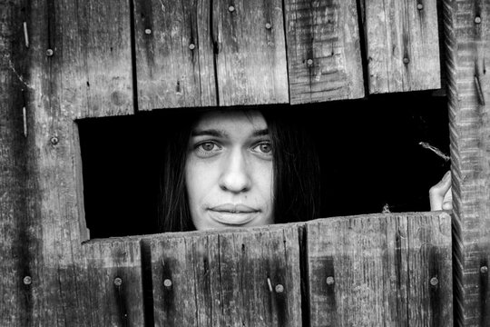 Young woman looking through the crack of a locked wooden shed, close-up. Black and white photo.