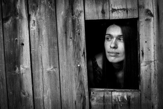 A young woman in a window ща wooden building. Black and white photo.