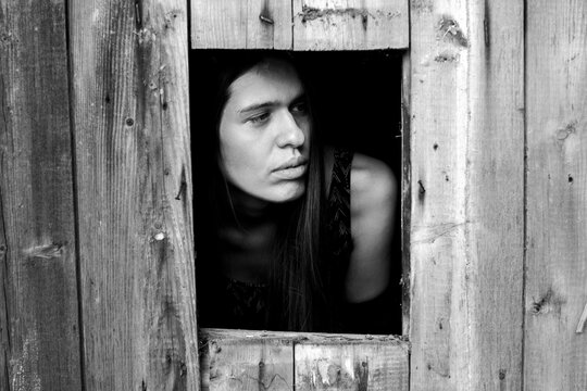 A young woman in a small window. Black-and-white photo.