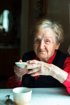 An old woman sits drinking tea, a portrait of grandmother in her home.