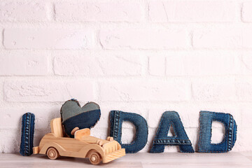 Obraz Father's day message from denim letters with wooden toy car on a white brick wall background. - fototapety do salonu