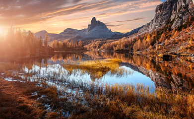 Magic sunny morning scene in autumn forest. Splendid Alpine lake in mountain valley with majestic rocky mount on background. Amazing nature landscape. Wonderful natural background. Vivid wallpaper
