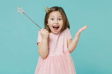 Little fun kid girl princess 5-6 years old wears pink dress crown diadem hold magic wand fairy stick isolated on pastel blue color background child studio. Mother's Day love family lifestyle concept.