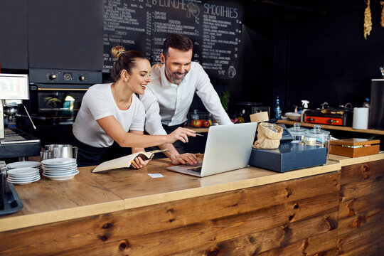 Two cafe owners working together planning supply orders on laptop