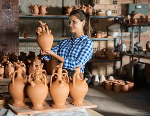 Fototapeta Portrait of female potter holding and inspecting ceramics in pottery workshop obraz