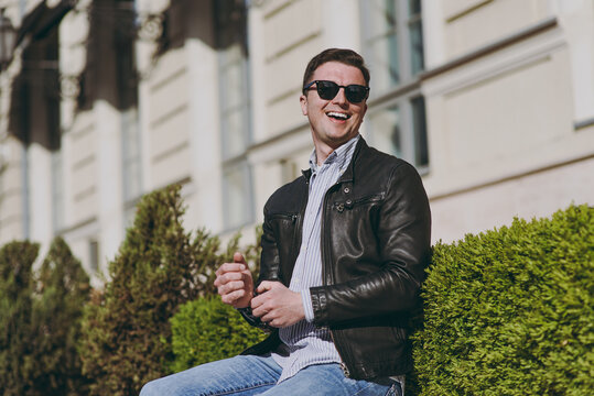 Young fashionable trendy smiling caucasian happy man 20s wearing black leather jacket eyeglasses sitting near bulding and bushes, resting in city downtown outdoors. Concept of people urban lifestyle