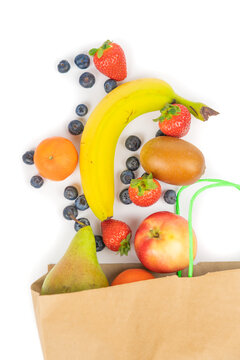 Many different types of fruit that roll out of a paper bag