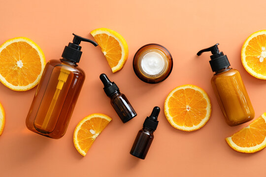 Flat lay vitamin c serum in dropper bottles, jar or cream, shower gel, shampoo with sliced orange. Top view natural fruit cosmetics.