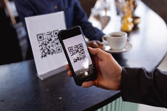 Mid section of man making a payment by scanning qr code from smartphone at a cafe