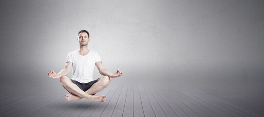 Man sitting in yoga lotus position with closed eyes in fitness studio. Relaxation and meditation concept with mockup place.