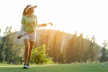 Golfer sport course golf ball fairway. People lifestyle woman relax after swing golf ball on the green. Asia female player game shot in summer. Healthy and Sport outdoor