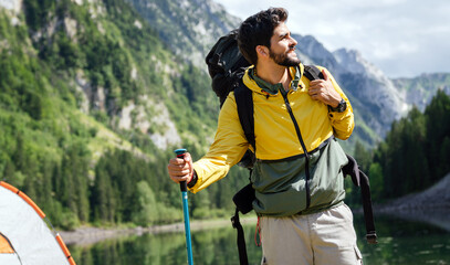 Fototapeta Hiker young man with backpack and trekking poles looking at the mountains in outdoor obraz