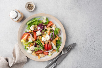 Italian summer salad Panzanella with tomatoes, mozzarella cheese and bread on grey concrete table background, top view, copy space