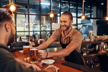 Charming young bartender in apron serving beer and smiling while working in the pub - fototapety na wymiar
