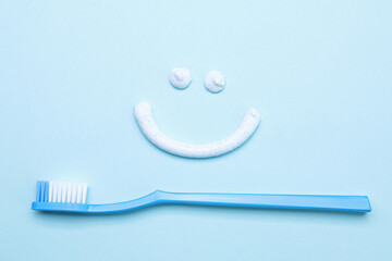 Funny face made with toothpaste and brush on light blue background, flat lay - fototapety na wymiar