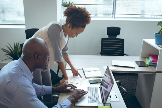 Two diverse male and female business colleagues sitting at desk and using laptop