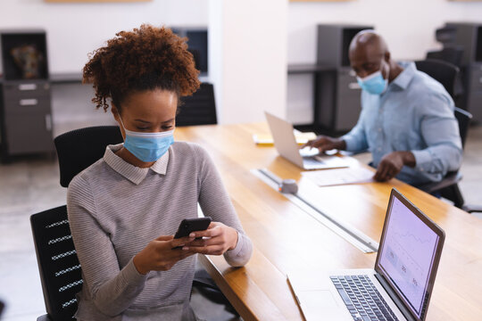 Two diverse male and female business colleagues wearing face masks using laptop and smartphone