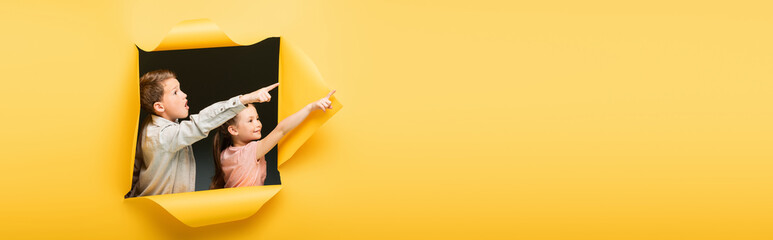 kids pointing away with fingers through hole on yellow background, banner. - fototapety na wymiar