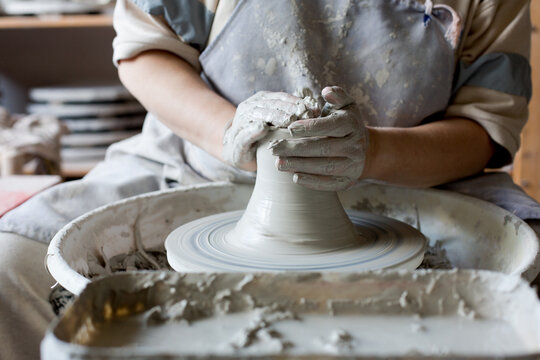 Woman making pottery on spinning wheel in her workshop