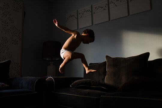 boy in underwear jumps across couches at home