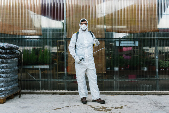 Man wearing a professional protective coverall to fumigate plant