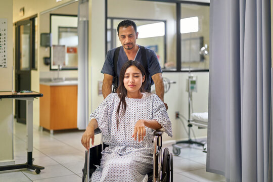 Healthcare: patient in a wheelchair by nurse assistant