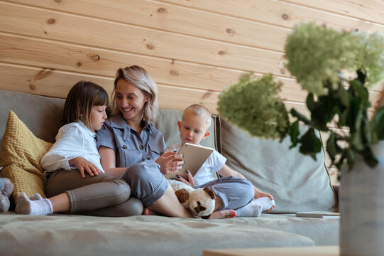 Cheerful mother with tablet communicating with kids on sofa