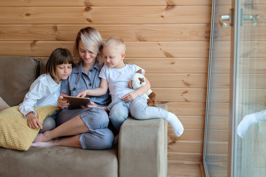 Woman and children relaxing on couch with tablet
