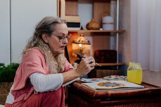 Close-up of senior woman painting mandalas with watercolors
