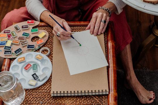 Top view of senior woman painting mandalas with watercolors