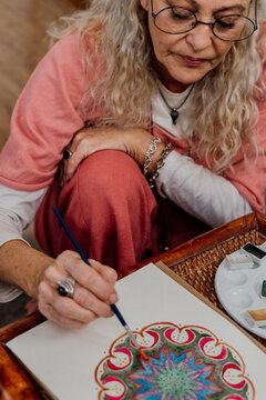 Portrait of senior woman painting mandalas at home