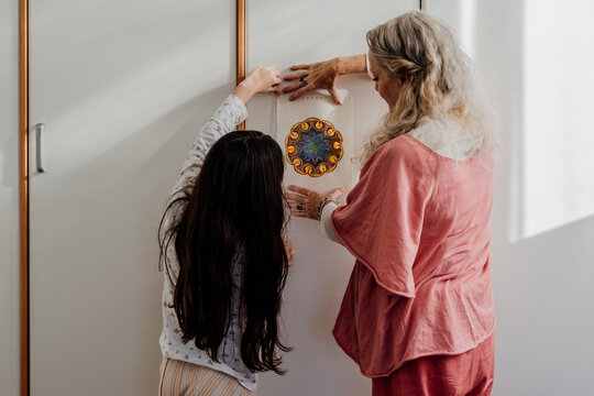 grandmother and grandaughter hanging a mandala painting