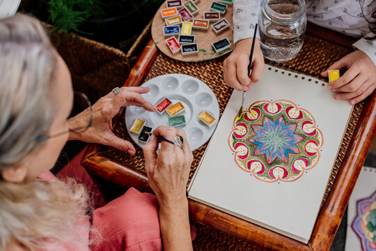 Little kid painting mandalas with her grandmother at bedroom