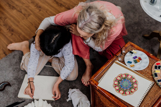 grandmother painting mandala with her granddaughter at bedroom