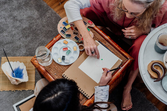 grandmother painting mandala with her granddaughter at room