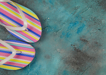 Top view on isolated pair colorful striped flip flops on blue background with copy space