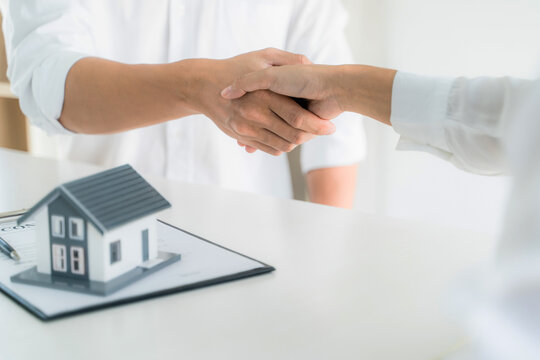 home loan insurance..Real estate broker and clientsign contract insurance agreement document. Business meeting concept