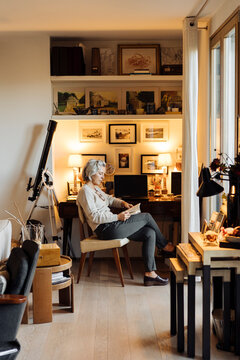Thoughtful woman reading book at home