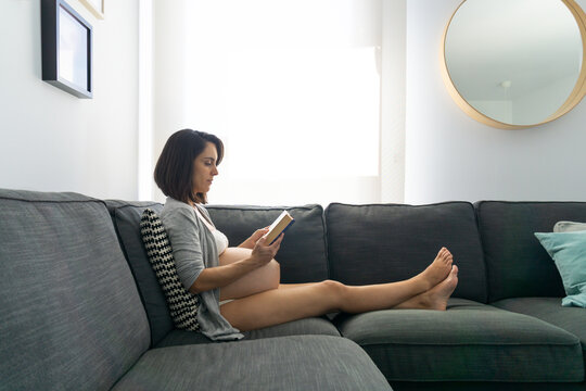 Pregnant woman sitting on the couch reading a book in her living room