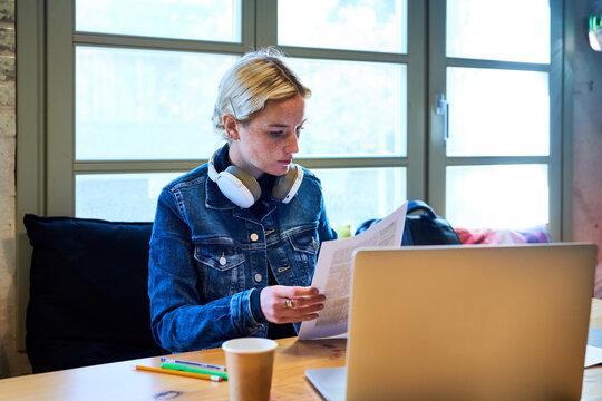 Blonde worker reading document.