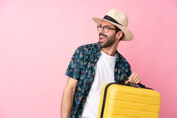 Fototapeta Young caucasian man over isolated background in vacation with travel suitcase and a hat obraz