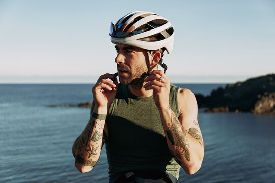 Cyclist putting on his helmet before a ride