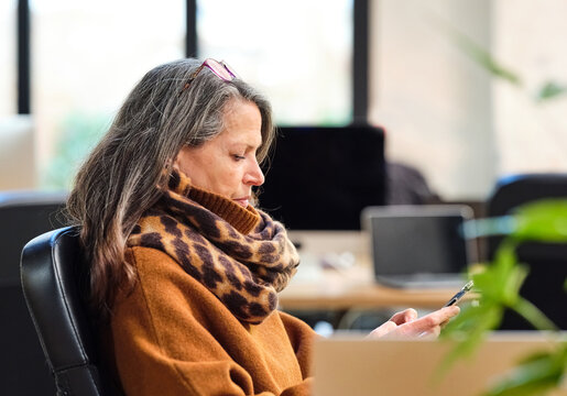 Senior woman checking smartphone in office