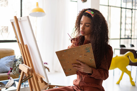 Mixed race Woman painting a picture on her home-studio.