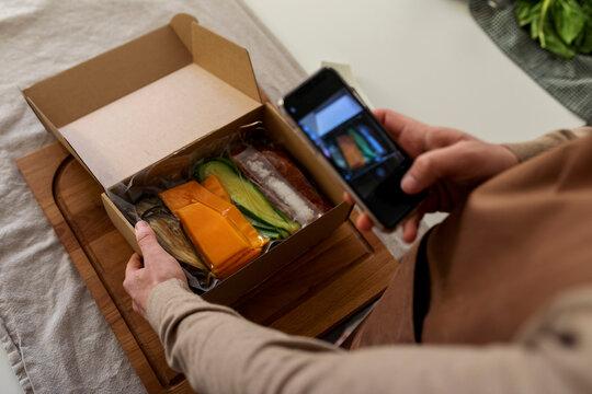 man taking picture of food box kit