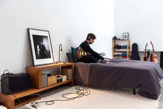 Guitarist with laptop having music practice at home