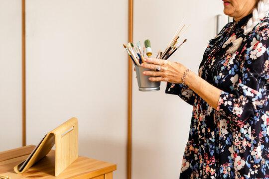 Senior woman picking up brushes to make crafts at home