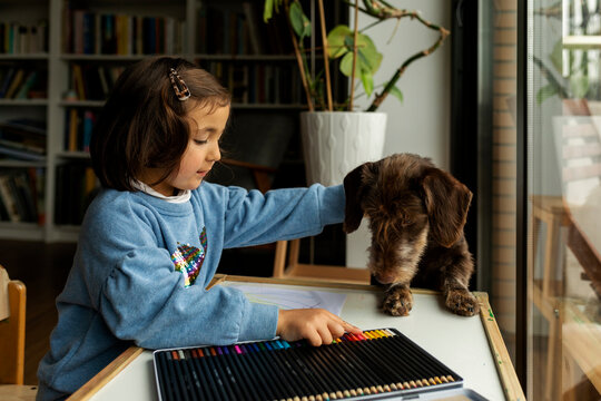happy little girl drawing with her puppy