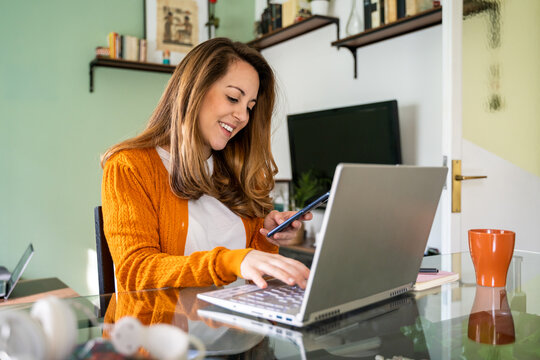 Young woman working from home in living room checking phone and tipying on laptop