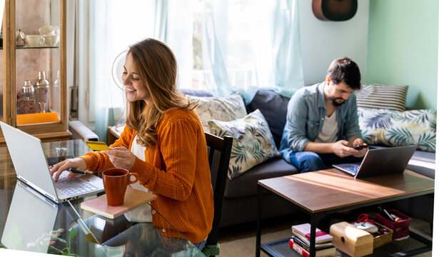 Young couple working from home in living room